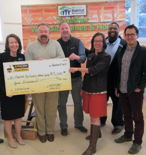 APM employees presenting donation to Habitat for Humanity