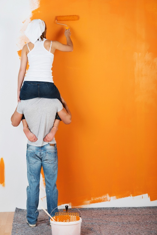 Couple painting wall home equity improvement fun